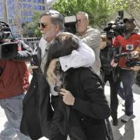 Photo - Casey Anthony is protected from the media by her attorney Cheney Mason as she arrives at the United States Courthouse for a bankruptcy hearing Monday, March 4, 2013, in Tampa, Fla. Anthony has not been seen in public since being acquitted in 2011 of murdering her two-year-old daughter Caylee. (AP Photo/Chris O'Meara)