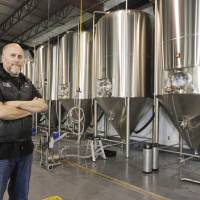 Photo -  JD Merryweather, co-founder of COOP Ale Works, stands with the fermenter tanks in the background at the new location for COOP Ale Works, 4745 Council Heights Road, in Oklahoma City. Photo by Paul B. Southerland, The Oklahoman   PAUL B. SOUTHERLAND -  PAUL B. SOUTHERLAND