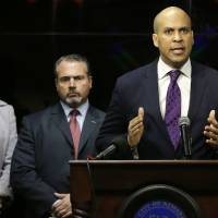 Photo - Newark Mayor Cory Booker responds at a news conference, Wednesday, Feb. 13, 2013 in Newark,  regarding a video that surfaced showing a naked young man being whipped because of his father's debt.  The men identified are 22-year-old Ahmad Holt, 31-year-old Raheem Clark and 23-year-old Jamaar Gray. Police say Holt administered the beating, using a belt provided by Clark. Charges include robbery and aggravated assault.   The video shows a 21-year-old man being forced to strip and then whipped with a belt, supposedly because his father owed someone $20. Subsequent to the police investigation, Nicole A. Smith was arrested for drug possession. (AP Photo/Mel Evans)