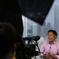 Photo - Jeff Floro, a hobbyist director, speaks during an interview in Hong Kong Friday, July 12, 2013. It was shot in single takes with amateur actors, hobbyist directors and about $650 - mainly to book a room in the same Hong Kong hotel that briefly housed National Security Agency leaker Edward Snowden. Floro said he and the other directors, Edwin Lee, Shawn Tse and Marcus Tsui, had only wanted to hone their guerrilla filmmaking style and produce something that was relevant to Hong Kong at that time. (AP Photo/Kin Cheung)