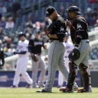 Photo - Miami Marlins catcher Miguel Olivo, right, visits pitcher Jose Fernandez after he walked Minnesota Twins' Joe Mauer in the first inning in the first game of a day/night double header, Tuesday, April 23, 2013 in Minneapolis, Minn. (AP Photo/Jim Mone)