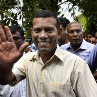 Photo -   FILE - In this Feb. 10, 2012 file photo, Maldives' former President Mohamed Nasheed waves as he walks back home after prayers in Male, Maldives. Police in the Maldives arrested Nasheed on Monday, Oct. 8, 2012, after he twice failed to appear before a court to face charges that he illegally ordered the arrest of a judge while in office. (AP Photo/Sinan Hussain, File)