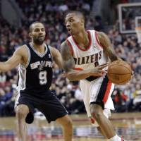 Photo - Portland Trail Blazers guard Damian Lillard, right, drives past San Antonio Spurs guard Tony Parker during the first quarter of an NBA basketball game in Portland, Ore., Thursday, Dec. 13, 2012. (AP Photo/Don Ryan)
