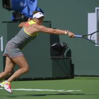 Photo - Vera Zvonareva, of Russia, returns a shot against Peng Shuai, of China, during a first round match at the BNP Paribas Open tennis tournament, Wednesday, March 5, 2014, in Indian Wells, Calif. (AP Photo/Mark J. Terrill)