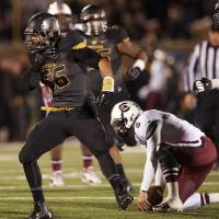 Photo - Missouri's Shane Ray, left, celebrates after sacking South Carolina quarterback Connor Shaw, right, during the third quarter of an NCAA college football game Saturday, Oct. 26, 2013, in Columbia, Mo. (AP Photo/L.G. Patterson)