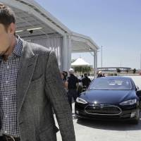 Photo - FILE - In this Friday, June 22, 2012 file photo, Tesla CEO Elon Musk walks past the Tesla Model S after a news conference at the Tesla factory in Fremont, Calif. Five states are on the short list for a $5 billion factory that Tesla Motors plans to build so it can crank out batteries for a new generation of electric cars. The package of economic incentives that each state offers will help determine where Tesla builds the factory — Nevada, California, Texas, Arizona or New Mexico. Tesla CEO Elon Musk has said the winning state will shoulder about 10 percent of the total cost, meaning at least $500 million worth of incentives.  (AP Photo/Paul Sakuma, File)