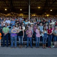 Photo - The crowd stands for the national anthem before the start of the Prescott Frontier Days rodeo, Wednesday, July 3, 2013 in Prescott, Ariz.  A mile-high city about 90 miles northwest of Phoenix, Prescott remains a modern-day outpost of the pioneer spirit. It's that spirit that will guide officials as they navigate the days ahead and figure out how to honor the elite Hotshot firefighters who died in a nearby wind-driven wildfire that is still burning. (AP Photo/Julie Jacobson)