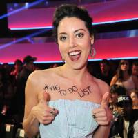 Photo - Actress Aubrey Plaza poses in the audience at the MTV Movie Awards in Sony Pictures Studio Lot in Culver City, Calif., on Sunday April 14, 2013. Plaza was thrown out of the show after trying to take away an award presented to Will Ferrell during the show. With the titled of her new movie scrawled across her chest, Plaza approached the stage as Ferrell made his acceptance speech after winning the Comedic Genius award. Jordan Strauss | Invision | AP