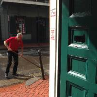 Photo - After a shooting on Bourbon Street, an apparent gunshot hole is seen in a door, at right, of the Bourbon Heat night club, as one employee sweeps up the sidewalk outside, early Sunday, June 29, 2014, in New Orleans. Nine people were shot on Bourbon Street in New Orleans' celebrated French Quarter, leaving at least one person in critical condition. (AP Photo/NOLA.com/The Times-Picayune, Benjamin Alexander-Bloch) MAGS OUT; NO SALES; USA TODAY OUT; THE BATON ROUGE ADVOCATE OUT
