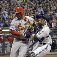 Photo - Milwaukee Brewers catcher Jonathan Lucroy, right, tags out St. Louis Cardinals' Jhonny Peralta at home during the fourth inning of the MLB National League baseball game Tuesday, April 15, 2014, in Milwaukee. Peralta tried to score from second on a hit by Peter Bourjos. (AP Photo/Morry Gash)