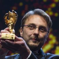 Photo - Director Calin Peter Netzer holds the Golden Bear for his film Child's Pose at the closing ceremony at the 63rd edition of the Berlinale, International Film Festival in Berlin, Saturday, Feb. 16, 2013. (AP Photo/Gero Breloer)