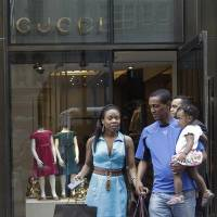 Photo - In this July 19, 2012 photo, a couple leaves the Gucci children's boutique on Fifth Avenue, in New York. Gucci's two-level children's boutique on New York's Fifth Avenue, next door to its adult flagship, may have brass teddy bears on the walls and plush child-sized furniture, but the prices for the miniature looks are hardly child's play. (AP Photo/Mary Altaffer)