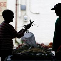 Photo -  A shopper purchases green beans during the Edmond Farmers Market at Festival Market Place. PHOTO BY PAUL HELLSTERN, THE OKLAHOMAN   PAUL HELLSTERN -