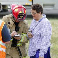 Photo - Norman fire officials interview the driver of a truck that caught fire on Interstate 35 on Wednesday, July 10, 2013 in Norman, Okla.  STEVE SISNEY - Steve Sisney