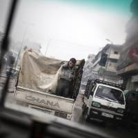 Photo - A boy is seen through a car window as he rides on the back of a truck in the streets of Aleppo, Syria, Saturday, Jan. 5, 2013. The revolt against President Bashar Assad that started in March 2011 began with peaceful protests but morphed into a civil war that has killed more than 60,000 people, according to a recent United Nations recent estimate. (AP Photo/ Andoni Lubaki)