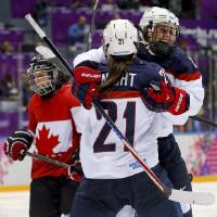 Photo - Hilary Knight of the United States (21) celebrates with teammate Kelli Stack (16)  after Alex Carpenter of the United States (25) scored a goal against Canada during the third period of the women's gold medal ice hockey game at the 2014 Winter Olympics, Thursday, Feb. 20, 2014, in Sochi, Russia. (AP Photo/Mark Humphrey)