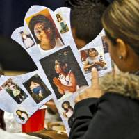 Photo - Family members look at photos of homicide victim Jasmen Gonzalez during a benefit dinner for the family of  at John Glenn Elementary on Wednesday, Nov. 16, 2011. in Oklahoma City, Okla..  Photo by Chris Landsberger, The Oklahoman  ORG XMIT: KOD