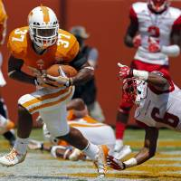 Photo - Tennessee defensive back Brian Randolph (37) returns an interception from the end zone as Western Kentucky receiver  Joel German (6) tries to tackle him in the second quarter of an NCAA college football game on Saturday, Sept. 7, 2013 in Knoxville, Tenn. (AP Photo/Wade Payne)