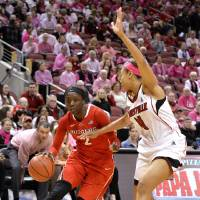 Photo - Rutgers' Kahleah Copper, left, attempts to drive around the defense of Louisville's Antonita Slaughter during the first half of an NCAA college basketball game Sunday, Feb. 23, 2014, in Louisville, Ky. (AP Photo/Timothy D. Easley)