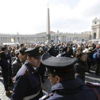 Photo - FILE -- In this file photo taken on Feb. 24, 2013, policeman patrol as faithful gather the last Angelus noon prayer of Pope Benedict XVI, celebrated from the window of his studio overlooking St. Peter's square at the Vatican. Planning for the moment when the next pope is proclaimed to the world, and for the installation ceremony a few days later, is a big-time guessing game. And that adds up to an ungodly logistical headache for the city of Rome. Nearly everything went smoothly for Benedict's last public appearances, although some faithful panicked during the retired pope's penultimate Sunday blessing from his studio window, when thousands of last-minute arrivals tried to squeeze through three narrow openings through a metal fence ringing the edge of the square. (AP Photo/Alessandra Tarantino)