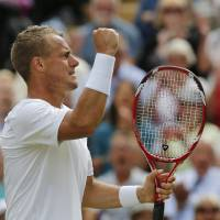 Photo - Lleyton Hewitt of Australia celebrates after winning a game against Jerzy Janowicz of Poland during their men's singles match at the All England Lawn Tennis Championships in Wimbledon, London, Friday, June 27, 2014.Janowicz won the match over five sets. (AP Photo/Ben Curtis)