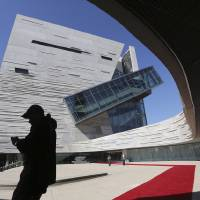 Photo -   Visitors walk outside the front entrance of the of the Perot Museum of Nature and Science during a media preview in Dallas, Wednesday, Nov. 14, 2012. The museum set to open Dec. 1 was named for billionaire former presidential candidate Ross Perot and his wife, Margot, after their five children made a $50 million gift in honor of them. (AP Photo/LM Otero)