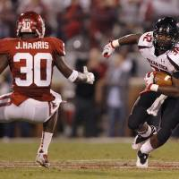 Photo - Texas Tech's Aaron Crawford (32) runs past Oklahoma's Javon Harris (30) during the college football game between the University of Oklahoma Sooners (OU) and Texas Tech University Red Raiders (TTU) at the Gaylord Family-Oklahoma Memorial Stadium on Saturday, Oct. 22, 2011. in Norman, Okla. Photo by Chris Landsberger, The Oklahoman  ORG XMIT: KOD