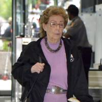 Photo - FILE - In this May 17, 2013 file photo, Jacqueline Goldberg, 87, who has accused Donald Trump of cheating her in a skyscraper condo deal, leaves the federal building in Chicago after testifying against Trump in her lawsuit. The attorney for Goldberg told jurors Wednesday, May 22, 2013, that he was personally repulsed by the