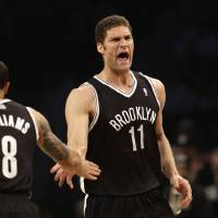 Photo - Brooklyn Nets' Brook Lopez, right, reacts after scoring against the Chicago Bulls during the first quarter of Game 1 of a first-round series of the NBA basketball playoffs, Saturday, April 20, 2013, in New York. (AP Photo/Seth Wenig)