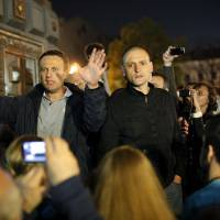Photo -   CORRECTS SPELLING OF SERGEI - Alexei Navalny, a prominent anti-corruption whistle blower and blogger, left, and opposition leader Sergei Udaltsov speak to protesters gathered near the presidential administrations building in downtown Moscow early Tuesday, May 8, 2012, a day after Putin's inauguration. Vladimir Putin took the oath of office in a brief but regal Kremlin ceremony on Monday, while on the streets outside thousands of helmeted riot police prevented hundreds of demonstrators from protesting his return to the presidency. (AP Photo/Alexander Zemlianichenko Jr )