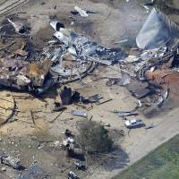 Photo - This aerial photo shows the remains of a fertilizer plant destroyed by an explosion and an emergency responders vehicle, bottom left, in West, Texas, Thursday, April 18, 2013. Rescuers searched the smoking remnants for survivors of Wednesday night's thunderous fertilizer plant explosion, gingerly checking smashed houses and apartments for anyone still trapped in debris while the community awaited word on the number of dead. (AP Photo/Tony Gutierrez)