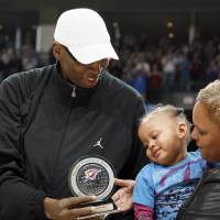 Photo - DEATH / DIED FRIDAY, MAY 15, 2009 / MUSICIAN / FORMER UNIVERSITY OF OKLAHOMA (OU) COLLEGE BASKETBALL / FORMER NBA BASKETBALL PLAYER /REGINA TISDALE / HONOR: Former University of Oklahoma (OU) college basketball star Wayman Tisdale shows his granddaughter, Bailey Braxton, and wife Regina, his Thunder Community Hero award during the NBA basketball game between Oklahoma City Thunder and San Antonio Spurs, Tuesday April 7, 2009, at the Ford Center in  Oklahoma CIty. Photo by Sarah Phipps, The Oklahoma ORG XMIT: KOD