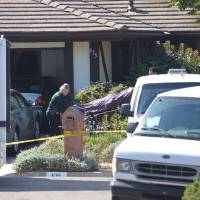 Photo - Investigators remove a body from a home in Goleta, Calif., Tuesday, Aug. 12, 2014, where four people and a dog were found stabbed to death the night before.  Authorities said the sole suspect, a 46-year-old man, was arrested without incident Tuesday. The names of the victims and suspect were being withheld pending notification of family. Goleta is a city of 30,000 people about 10 miles northwest of Santa Barbara.(AP Photo/The News-Press, Steve Malone)