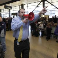 Photo -   Jim McBarron, manager of station perations for Alaska Airlines, uses a bullhorn to try and find passengers for a flight that was about to take off for San Diego, Monday, Oct. 8, 2012, during a system-wide outage of the computers the airline uses to check in passengers at Seattle-Tacoma International Airport in Seattle. Most flights were delayed or canceled, but the airline was able to manually check in passengers for a few of its flights. (AP Photo/Ted S. Warren)