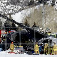 Photo - Emergency crews work near a passenger plane that crashed upon landing at the Aspen-Pitkin County Airport in Aspen, Colo., Sunday, Jan. 5, 2014. (AP Photo/The Aspen Times, Leigh Vogel)