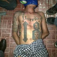 Photo - In this undated image obtained by the Associated Press on Feb. 14, 2013, a man lies on the ground surrounded by unidentified people. On Jan. 9, 2013, neighbors of Kevin Said Carranza Padilla, 28, known in the gang world as