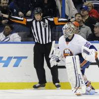 Photo - New York Islanders goalie Kevin Poulin (60) celebrates as referee Mike Leggo (3) signals no goal on a shot by Tampa Bay Lightning defenseman Victor Hedman, of Sweden, during a shoot out in an NHL hockey game, Thursday, Jan. 16, 2014, in Tampa, Fla. (AP Photo/Chris O'Meara)