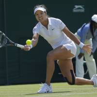 Photo - FILE - In this June 27, 2014 file photo, Li Na of China plays a return to Barbora Zahlavova Strycova of the Czech Republic during their women's singles match at the All England Lawn Tennis Championships in Wimbledon, London. Li is pulling out of the U.S. Open because of a knee injury. Li says Thursday, July 31, 2014, in a posting on Facebook that she has