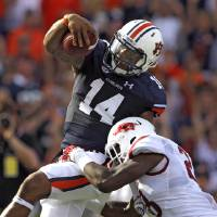 Photo - Auburn quarterback Nick Marshall (14) runs in for a touchdown as he is hit by Arkansas safety Josh Liddell (28) during the second half of an NCAA college football game on Saturday, Aug. 30, 2014, in Auburn, Ala. (AP Photo/Butch Dill)