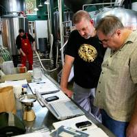 Photo - William Scott, right, and Choc Beer Co. Brewmaster Michael Lalli consult a computer containing plans for the Gratzer beer they brewed recently. Brewer B.J. Howell is also pictured. PHOTO BY NICK TROUGAKOS, THE OKLAHOMAN  unknown