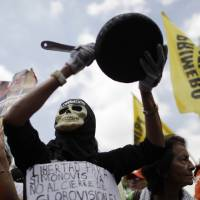 Photo - A protester dressed as a death holds up pan during an opposition demonstration against of the devaluation of the currency in Caracas, Venezuela, Saturday, Feb. 23, 2013. Venezuela's government announced on Friday, Feb. 8 that it is devaluing the country's currency, a long-anticipated change expected to push up prices in the heavily import-reliant economy. Venezuela's government has had strict currency exchange controls since 2003 and maintains a fixed, government-set exchange rate. While those controls have restricted the amounts of dollars available at the official rate, an illegal black market has flourished and the value of the bolivar has recently been eroding.  (AP Photo/Ariana Cubillos)
