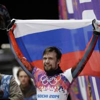 Photo - Alexander Tretiakov of Russia celebrates in the finish area after he won the gold medal during the men's skeleton competition at the 2014 Winter Olympics, Saturday, Feb. 15, 2014, in Krasnaya Polyana, Russia. (AP Photo/Natacha Pisarenko)