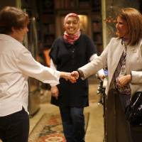 Photo - Marilyn Baragree, second from left,  greets Terri Angier, as Greg Smith,  left, and Sarah Albahadily watch before a 2012