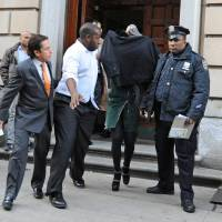 Photo - FILE - Lindsay Lohan, second from right, is escorted from the 10th Precinct police station, with her face shielded, in this Nov. 29, 2012 file photo taken in New York after being charged for allegedly striking a woman at a nightclub. Lohan is scheduled to appear in court Monday Jan. 7, 2013 to face assault charges in connection with the fight at a Manhattan nightclub. (AP Photo/ Louis Lanzano)