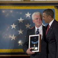 Photo - President Barack Obama stands with Ray Kapaun, nephew of Chaplain (Captain) Emil J. Kapaun, U.S. Army, as he awards the Medal of Honor posthumously to Chaplain Kapaun in the East Room of the White House in Washington, Thursday, April 11, 2013. Chaplain Kapaun will receive the Medal of Honor posthumously for his extraordinary heroism while serving with the 3d Battalion, 8th Cavalry Regiment, 1st Cavalry Division during combat operations against an armed enemy at Unsan, Korea and as a prisoner of war from November 1-2, 1950.(AP Photo/Carolyn Kaster)