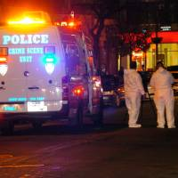 Photo - Police are investigating the deaths of a woman and two toddlers in the Queens borough of New York, Sunday, Jan. 19, 2014. Police say the bodies of a 1-year-old child, a 3-year-old child and a 21-year-old female were found in an apartment on Sutphin Blvd. in the Jamaica section of the borough. (AP Photo/David Torres)