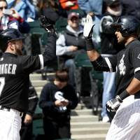 Photo - Chicago White Sox's Jeff Keppinger (7) greets Alex Rios at home after the pair scored on Rios' home run off Cleveland Indians starting pitcher Zach McAllister during the fifth inning of a baseball game Wednesday, April 24, 2013, in Chicago. (AP Photo/Charles Rex Arbogast)
