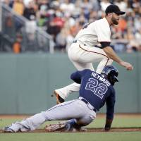 Photo - San Francisco Giants second baseman Brandon Hicks, top, turns a double play over Atlanta Braves' Jason Heyward (22) on a ground ball from Justin Upton during the first inning of a baseball game on Monday, May 12, 2014, in San Francisco. (AP Photo/Marcio Jose Sanchez)