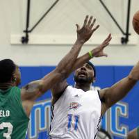 Photo - Oklahoma City Thunder's Lazar Hayward (11) shoots over Boston Celtic's Fab Melo (13) during an NBA summer league basketball game, Monday, July 9, 2012, in Orlando, Fla. (AP Photo/John Raoux) ORG XMIT: DOA108