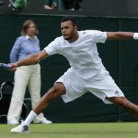 Photo - Jo-Wilfried Tsonga of France stretches to reach the ball as he returns to Juergen Melzer of Austria during their first round match at the All England Lawn Tennis Championships in Wimbledon, London, Monday, June 23, 2014. (AP Photo/Ben Curtis)